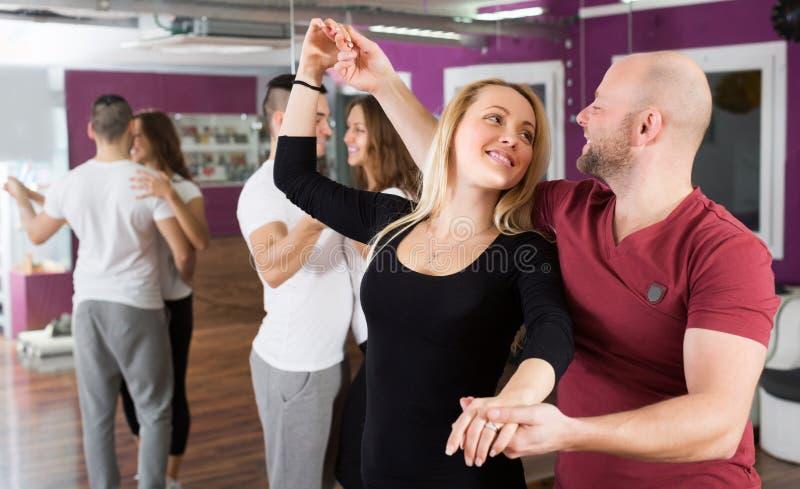 Kopplar ihop att tycka om av partnerdansen royaltyfria bilder