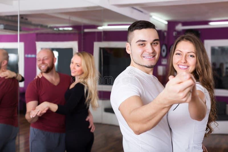 Kopplar ihop att tycka om av partnerdansen royaltyfri fotografi