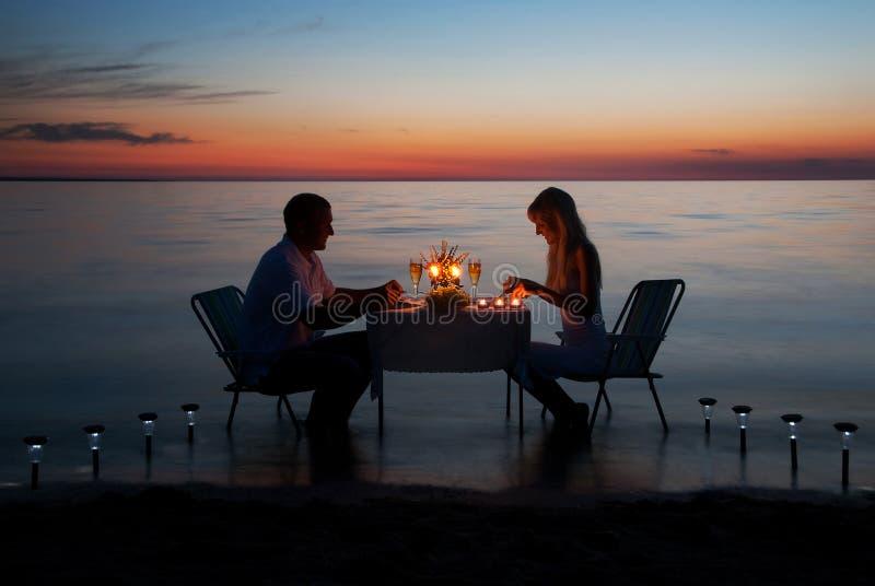 Kopplar ihop barn aktie en romantisk matställe med stearinljus på stranden fotografering för bildbyråer