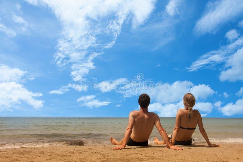 Kopplar ihop det attraktiva barnet att tycka om en romantisk flykt på stranden arkivbilder