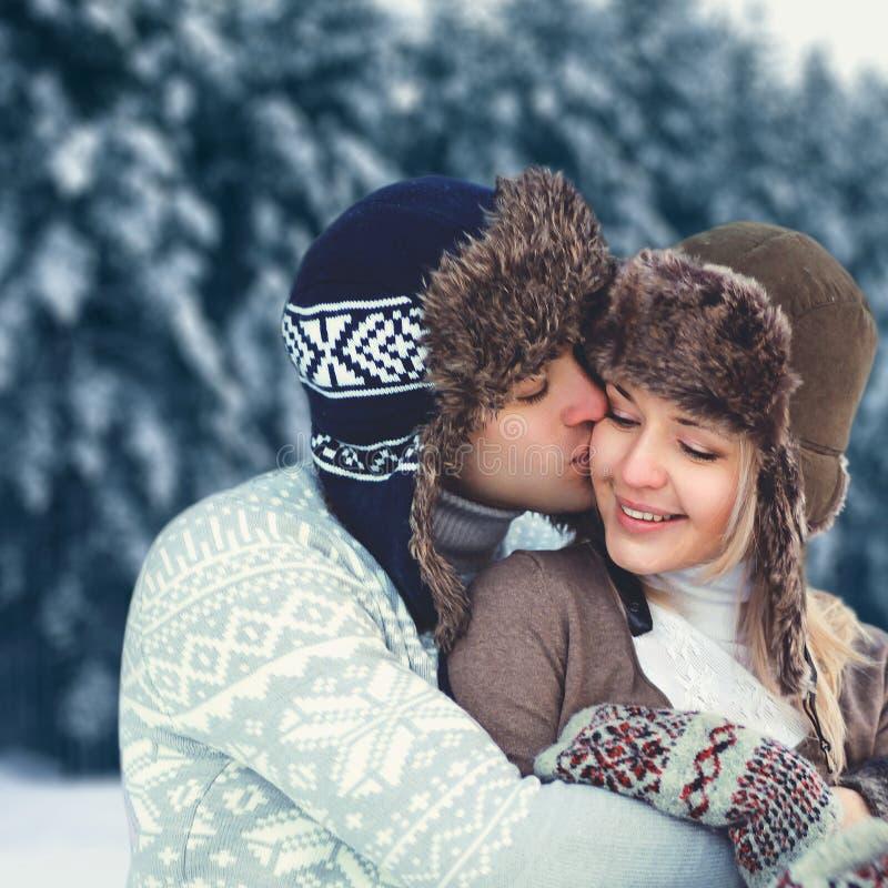Kopplar ihop man det lyckliga barnet för stående förälskat på vinterdagen, den bärande hatten för den försiktiga kyssande kvinnan royaltyfri bild