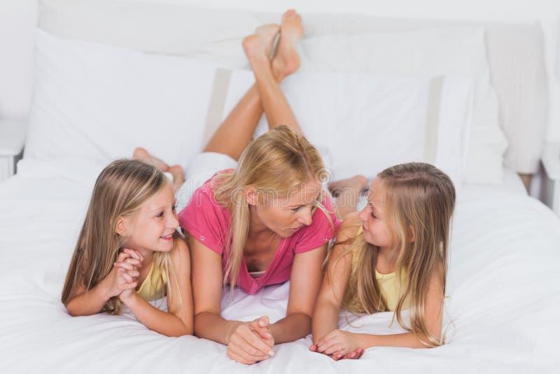 Kopplar samman att koppla av med deras moder i säng arkivbilder
