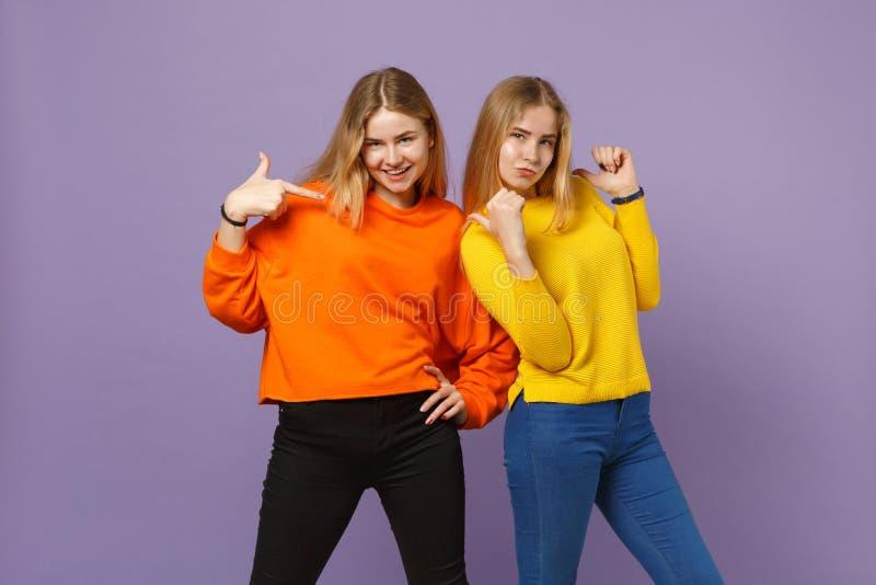 Kopplar samman rolig ung blondin två systerflickor i livlig färgrik kläder som pekar fingrar på dem på pastell arkivfoto