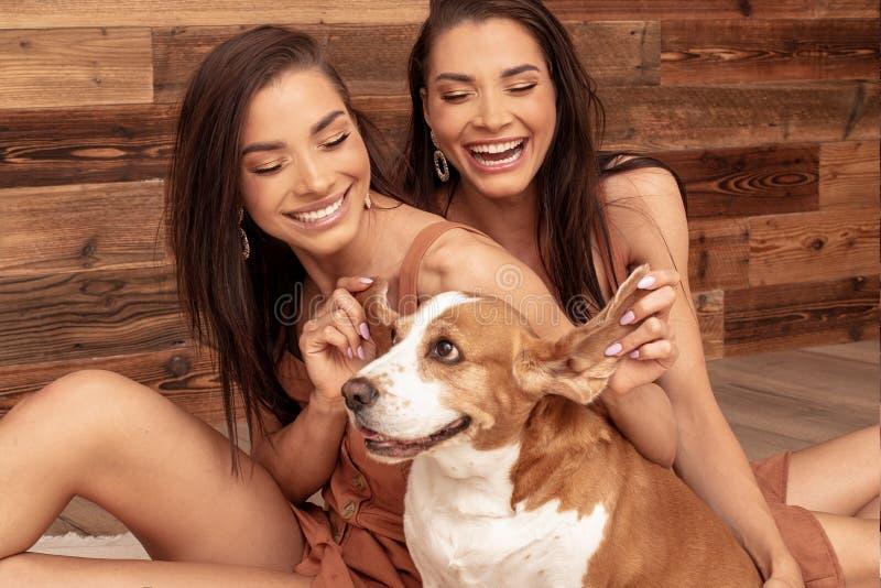 Kopplar samman systrar som spelar med den gulliga hunden som ler royaltyfri fotografi