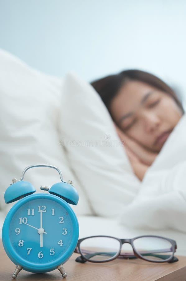 Kopplat av av den unga asiatiska kvinnan som sover på säng i vinter royaltyfria foton