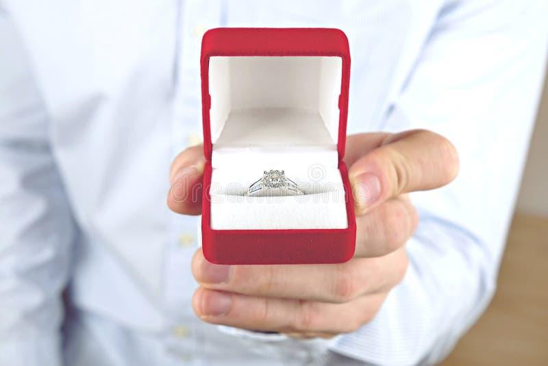 Kopplings-/förbindelse-/bröllopförslagplats Stäng sig upp av mannen som räcker den dyra guld- platinadiamantcirkeln till hans bru royaltyfri bild