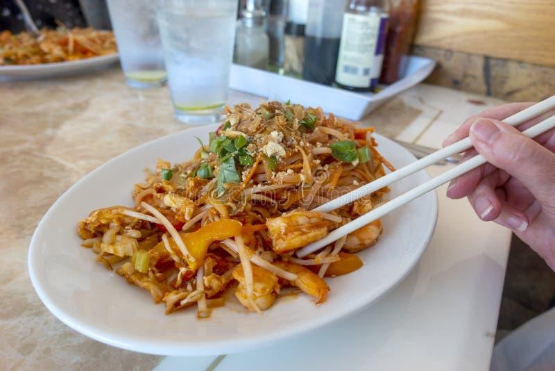 Kopsticks och räkor i thailändskt mjöl med färsk koriander royaltyfri fotografi