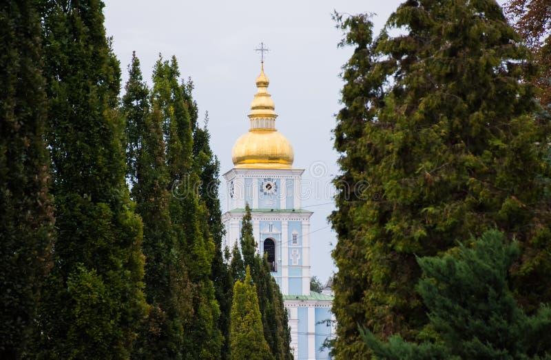 Kopuła z krzyżem i zegar kościół chrześcijański otaczający korytarzem drzewa - zieleni iglaści arborvitaes zdjęcia royalty free