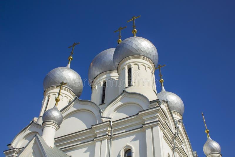 Kopuły biały ortodoksyjny kościół z złocistymi krzyżami przeciw błękitnemu jasnemu niebu, dolny widok fotografia stock