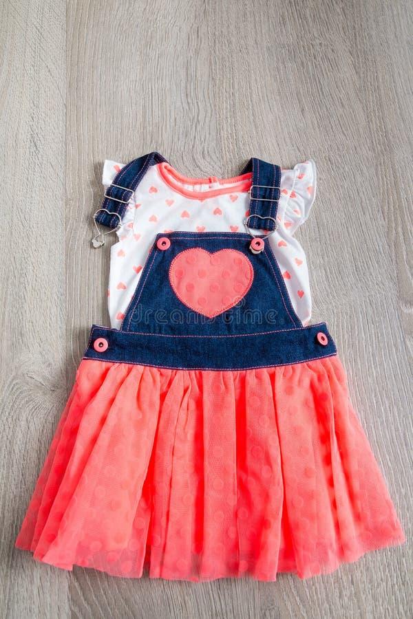 Koral i błękit ubieramy, kombinezony z sercem na popielatym drewnianym tle Mała dziewczynka strój Odgórny widok zdjęcie stock