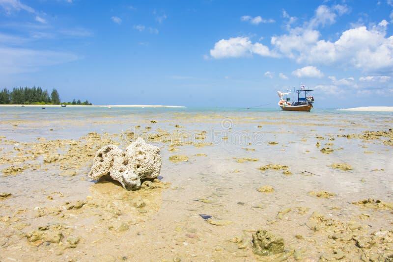 Korallenrotes und Fischerboot auf dem Strandmeerblick und -wolke stockbilder