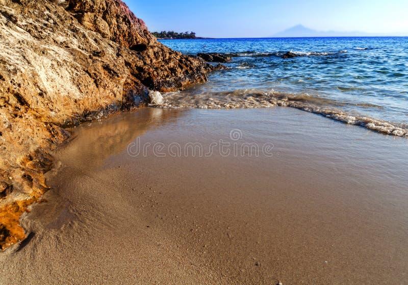 Korallstranden vaggar och det härliga havet med blå himmel på Grekland royaltyfria foton