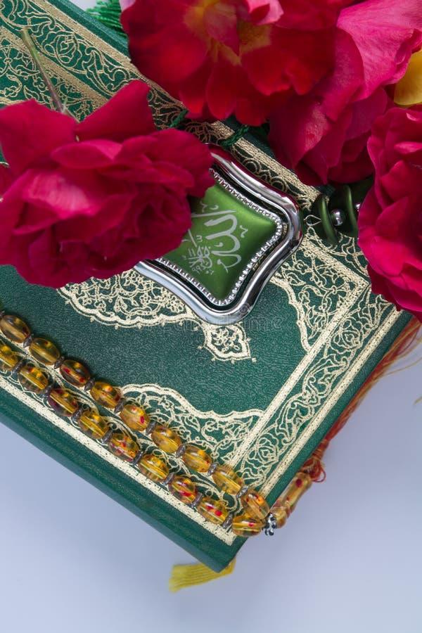 Koran και τριαντάφυλλα που απομονώνονται στο άσπρο υπόβαθρο στοκ φωτογραφία