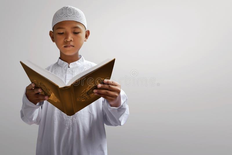 Koran asiático da leitura da criança dos muçulmanos foto de stock