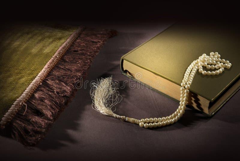Koran i modlitewni koraliki z modlitewną matą na podłodze obrazy royalty free