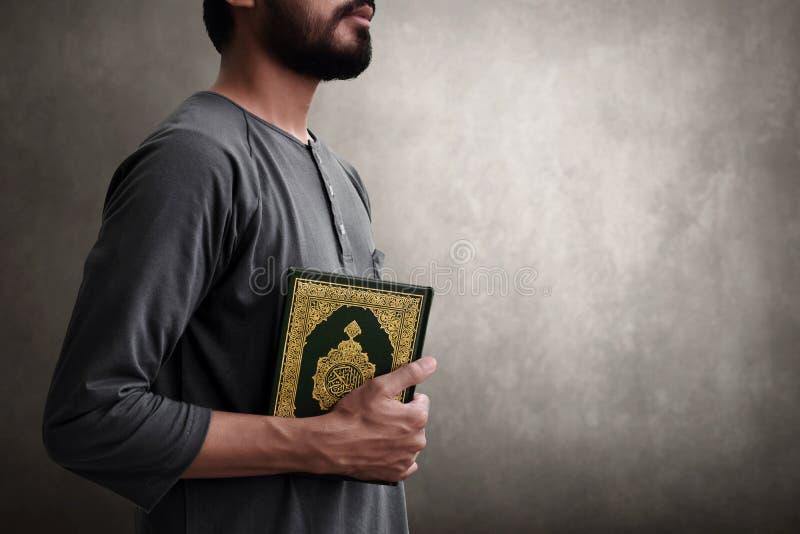 Koran muçulmano da terra arrendada do homem no fundo da parede fotografia de stock