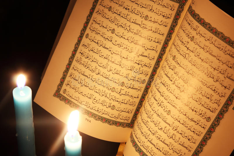 Koran or quran holy book with candles stock images