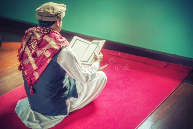 Koran santo leggente dell'uomo musulmano religioso dentro la moschea fotografia stock libera da diritti