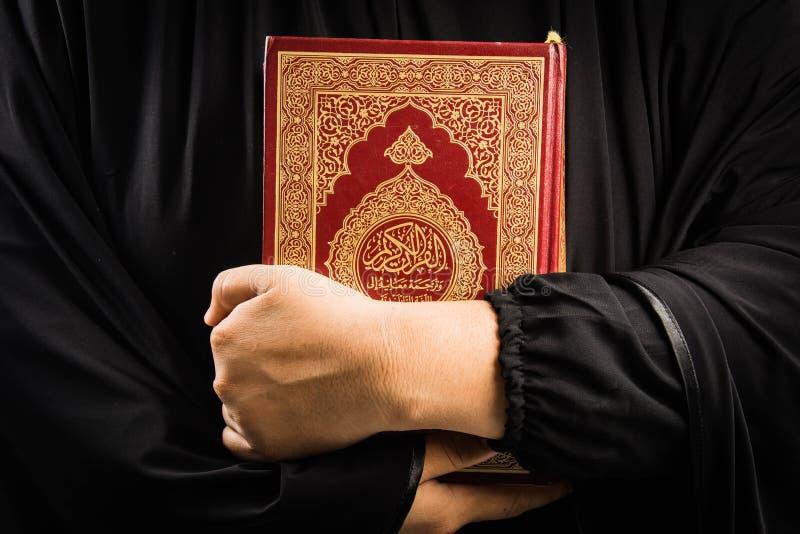 Koran ter beschikking - heilig boek van vrouw van de Koran in hand moslims van Moslims (openbaar punt van alle moslims) stock afbeeldingen