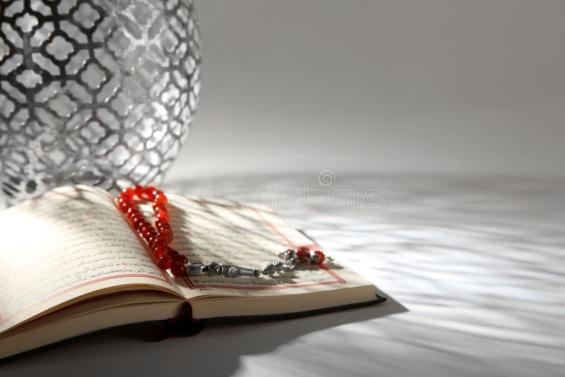Koran z Muzułmańskimi modlitewnymi koralikami na stole zdjęcia stock