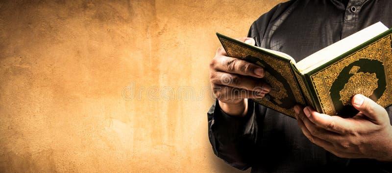 Koranen i handen - helig bok av muselmaner arkivbilder