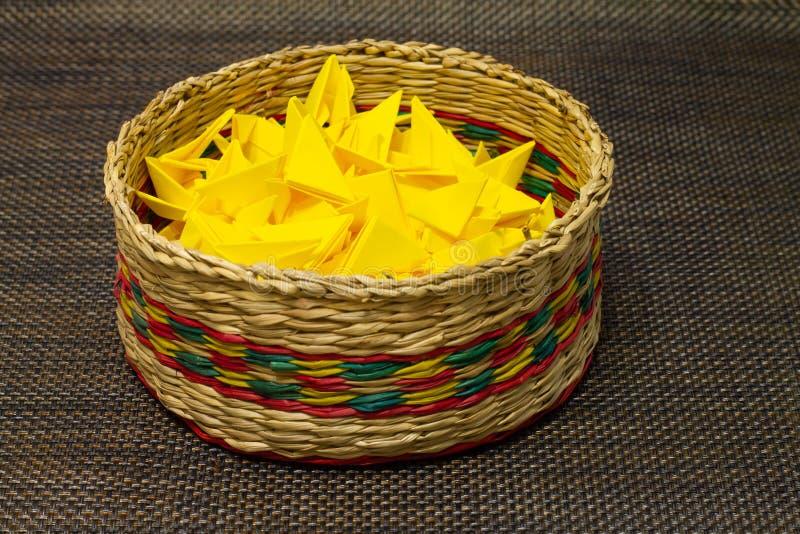 Korb des gesponnenen Strohs mit gelbem Papier stockfotografie