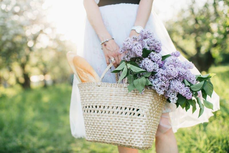Korb mit Blumenstrauß von Fliedern und von Stangenbrot in den Frauenhänden auf Hintergrund der Natur stockbilder