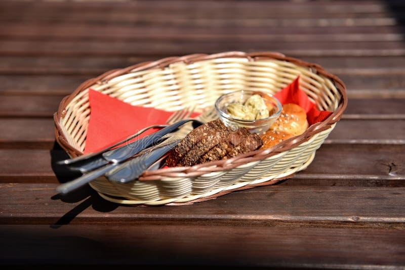 Korb mit Brot und Tischbesteck auf braunem Holztisch Selektiver Fokus stockbilder