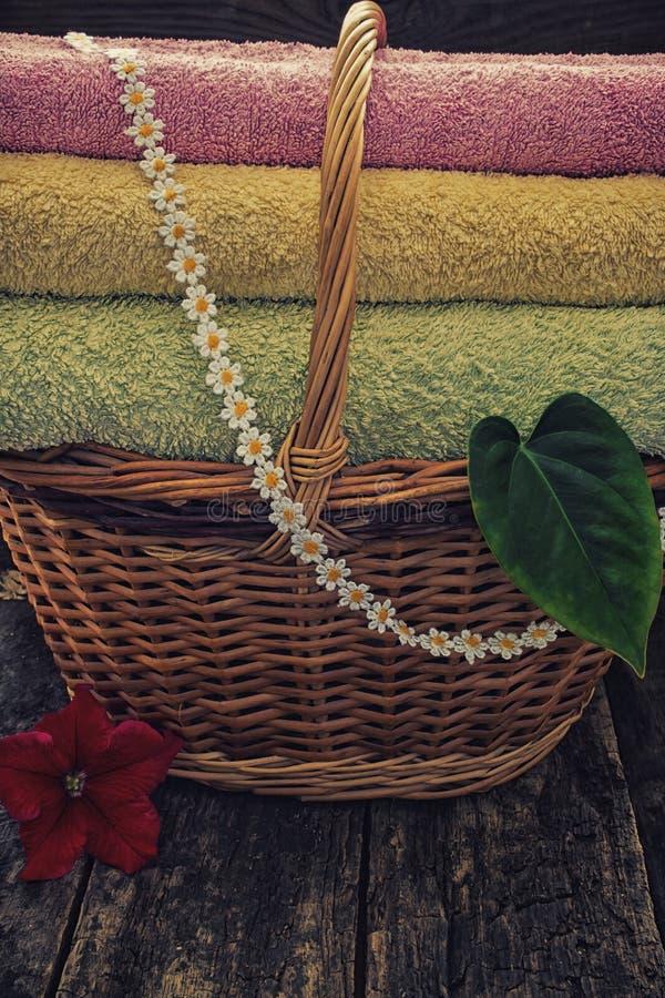 Korb mit bunter roter Blume der sauberen Tücher und grünem Blatt auf einem Retro- Filter des hölzernen Hintergrundes lizenzfreies stockbild