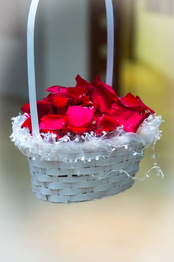 Korb mit den rosafarbenen Blumenblättern lizenzfreie stockbilder
