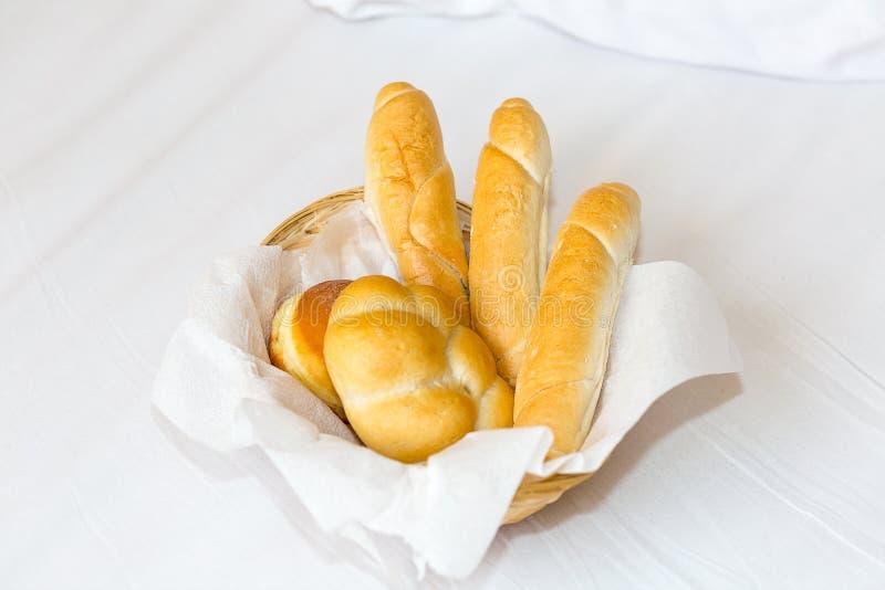 Korb mit drei Stangenbroten und ein reizendes Frühstück des Donuts beleuchten Snack des Mittagessens auf einem weißen Hintergrund stockfotografie