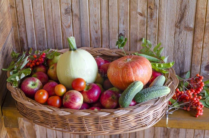 Korb mit Gemüse und Früchten auf einem hölzernen Hintergrund Ernten des Herbst- und Sommererntekürbises, Zucchini, Apfel stockbilder