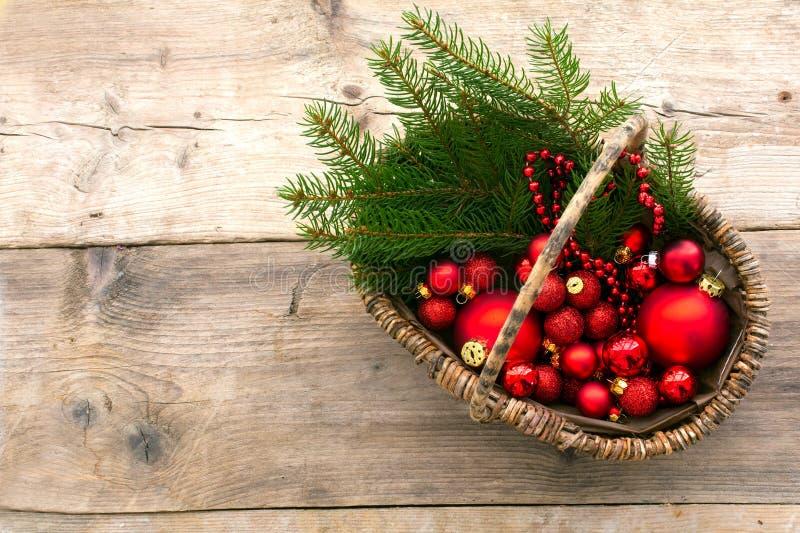 Korb mit rotem Weihnachtsflitter und -kiefer verzweigt sich von über O lizenzfreie stockfotografie