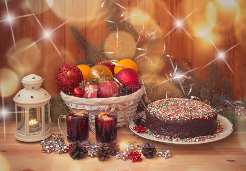 Korb mit Weihnachtsdekorationen und -früchte, Gläser Glühwein, Weihnachtskuchen und Laterne stockbilder
