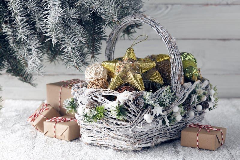 Korb mit Weihnachtsgeschenken und -dekorationen unter Tannenbaum stockbild