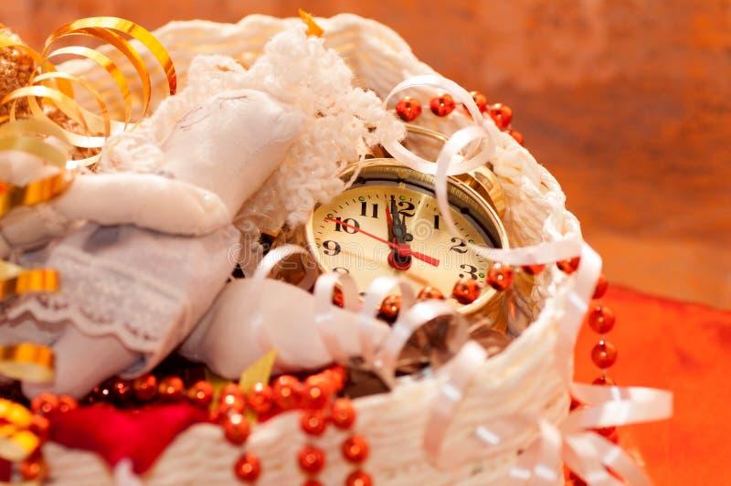 Korb mit Weihnachtsspielwaren und den Uhrhänden stockfotos