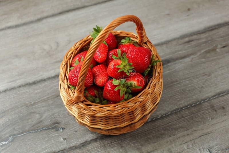 Korb voll von frisch ausgewählten Erdbeeren auf grauem hölzernem Schreibtisch lizenzfreies stockbild
