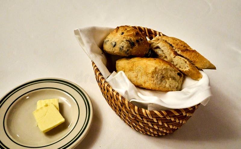 Korb von Broten und von Butter auf einer Platte gedient vor Hauptmahlzeit stockfotos