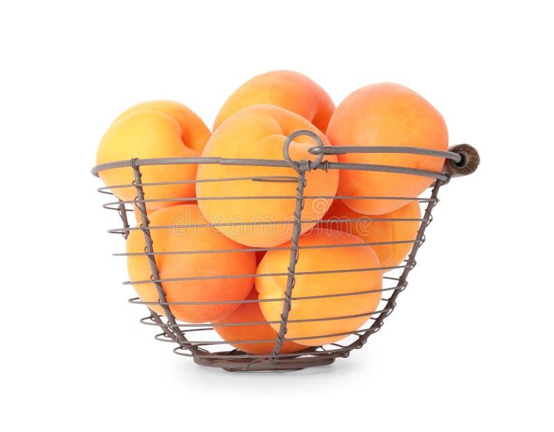 Korb von reifen Aprikosen auf Weiß lizenzfreie stockbilder