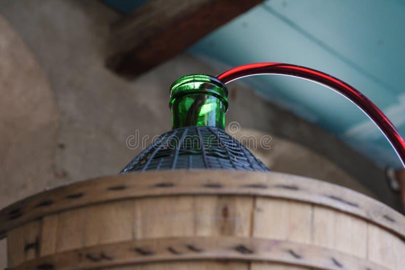 Korbflasche nah oben bei der Entleerung des Rotweins lizenzfreie stockbilder