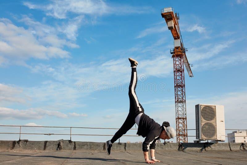 Koreański miastowy stylowy męski tancerza spełniania breakdance handstand na wierzchołka dachu zdjęcia stock