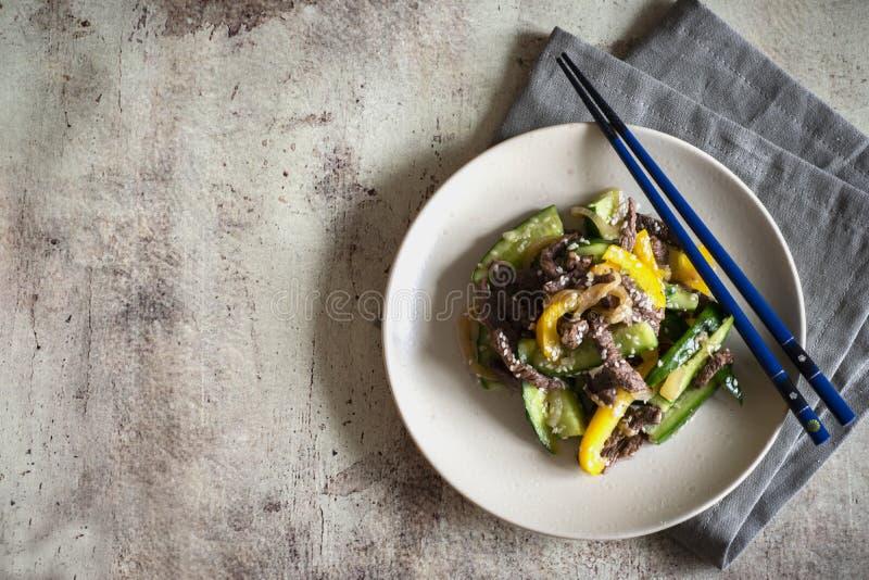 Koreański naczynie na szarym tle: korzenna sałatka z mięsem, pieprz, ogórki, pieprz, sezam na pięknym talerzu z pieluchą i obraz royalty free