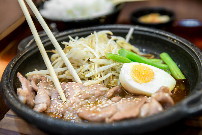 Koreaans kruidig die bbq varkensvlees op een warmhoudplaat met bijgerechten wordt gediend stock afbeeldingen