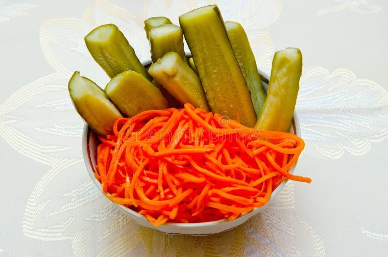 Koreaanse wortel en ingelegde die komkommer op een plaat wordt gesneden stock foto's