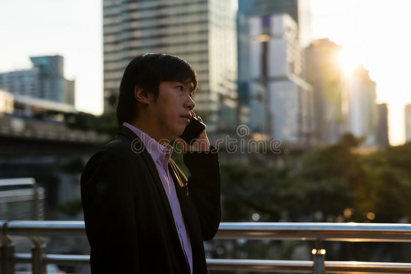 Korean businessman on phone in city at sunset royalty free stock image