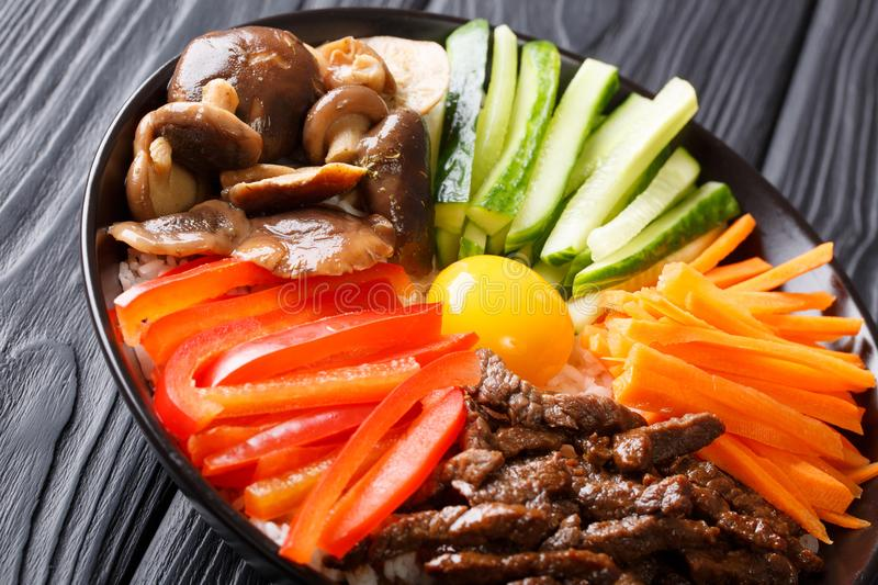 Korean food Bibimbap with fried beef, raw egg, vegetables, shiitake and rice close-up in a bowl. horizontal stock images