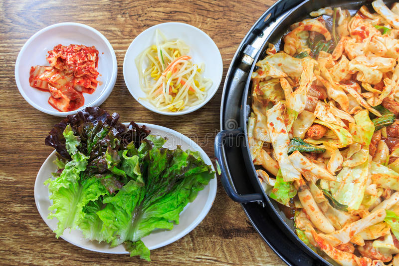 Korean food. Compose of kimchi, fresh lettuce, bean sprouts and stir-fried vegetables with chicken on wood table stock image