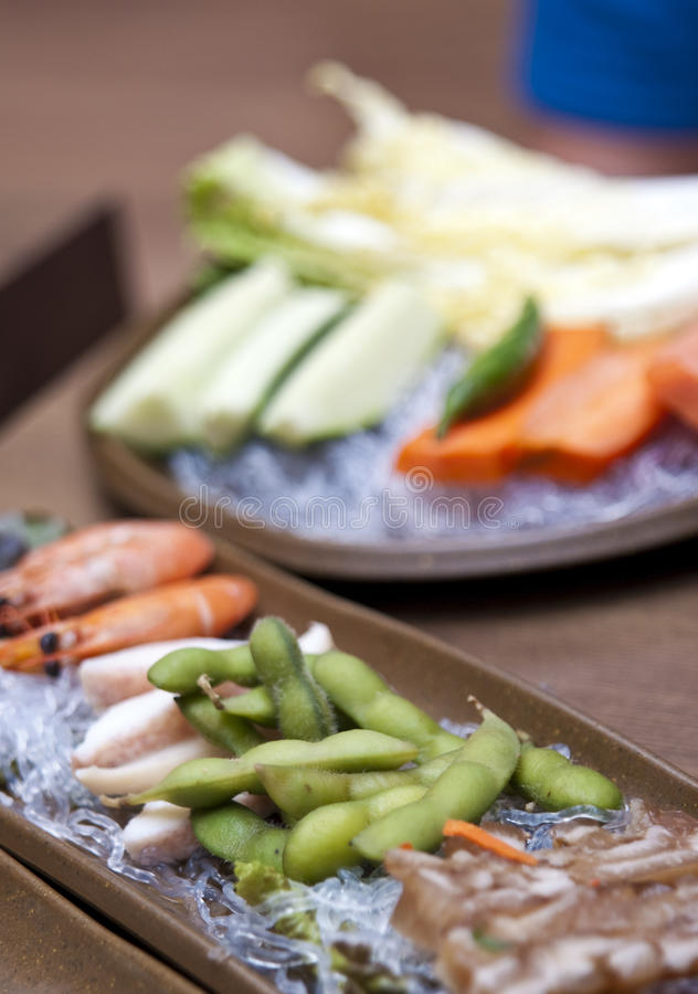 Korean food in restaurant. Typical South Korean food table setting in a restaurant. Assorted seafood and peas royalty free stock photos