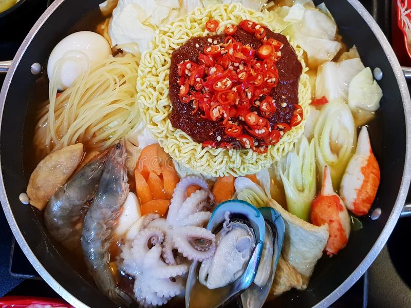 Korean food style,  Selective focus of Instant noodles with vegetable, pork sliced, mussel, squid and shrimp in hot pot on wooden. Table, Budae jiigae is Korea stock photography