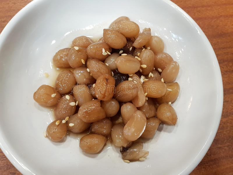 Korean food style, Top view of stir fried peanut topped with sesame seeds on white plate. stock images